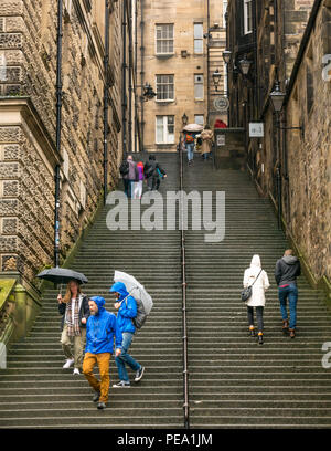 Tourists with umbrellas in rain walking up long steep steps in alley, Warriston's Close, Cockburn Street to Royal Mile, Edinburgh, Scotland, UK - Stock Photo