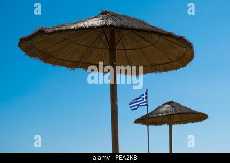 A Greek national flag with parasols on the beach. Glyfada, Athens, Greece. - Stock Photo