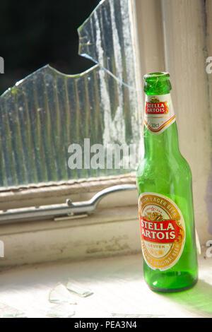 A bottle of Stella Artois beer sits on a window sill by a broken window - Stock Photo