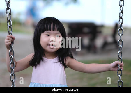 Portrait of a little asian girl in swing - Stock Photo