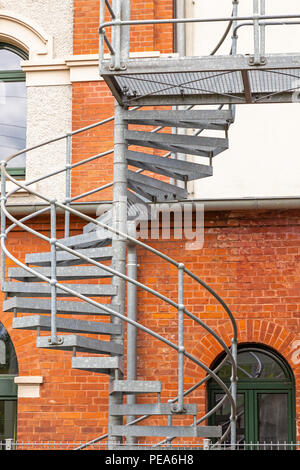 Spiral staircase made of metal on the brick facade of a renovated industrial building - Stock Photo