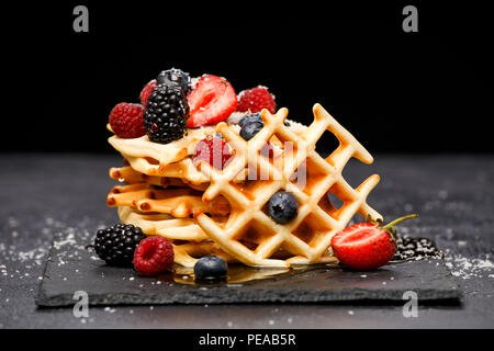 Photo of fresh viennese wafers with berries with powdered sugar on blackboard on blank background - Stock Photo