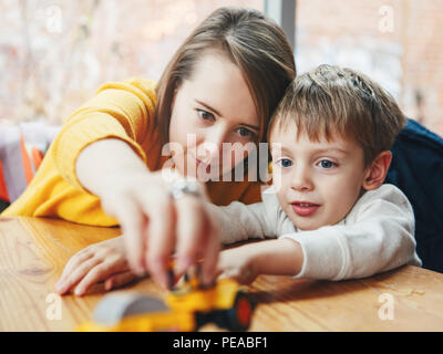 Portrait of white Caucasian happy family, mother and son, sitting in restaurant cafe at table, smiling playing with toy car, authentic lifestyle - Stock Photo