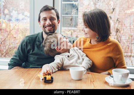Portrait of white Caucasian happy family of three mother, father and son, sitting in restaurant cafe at table, smiling playing, authentic lifestyle - Stock Photo