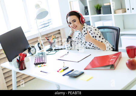 A beautiful young girl sits in headphones and with a microphone at the table in the office and shows a class sign. - Stock Photo