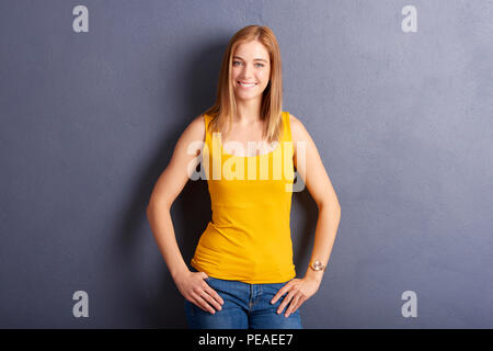 Portrait of beautiful young woman posing against at grey wall while looking at camera and smiling. - Stock Photo