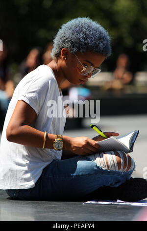 NEW YORK, NY - SEPTEMBER 02: Young black woman studying a book while sitting in Washington Square Park, Manhattan on September 2, 2016 in New York, US - Stock Photo