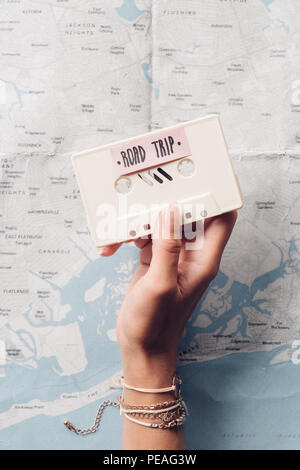 Cropped shot of woman holding retro audio cassette with map on background, road trip concept - Stock Photo