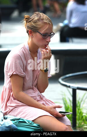 NEW YORK, NY - SEPTEMBER 05: Young white woman checks her phone while sitting in Washington Square Park, Manhattan on September 5, 2016 in New York, U - Stock Photo