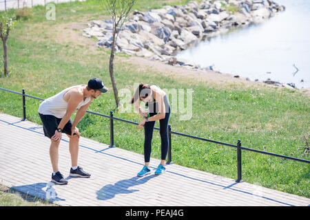High angle portrait of active young couple taking break to catch breath while running outdoors in park, copy space - Stock Photo