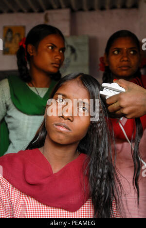 INDIA, New Delhi, Balika Ashram for former child labourer , vocational training for girls in beauty parlour , hair curling , making curly hair - Stock Photo