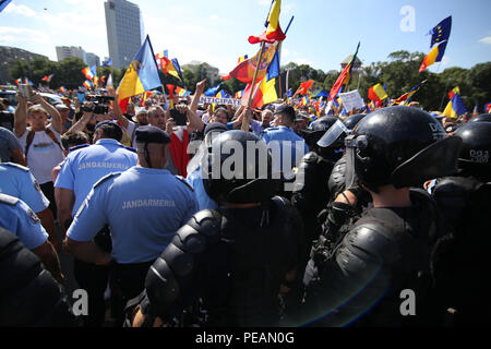 BUCHAREST, ROMANIA - August 10, 2018: Riot police spray teargas while scuffling with protesters outside the government headquarters. Romanians who liv - Stock Photo
