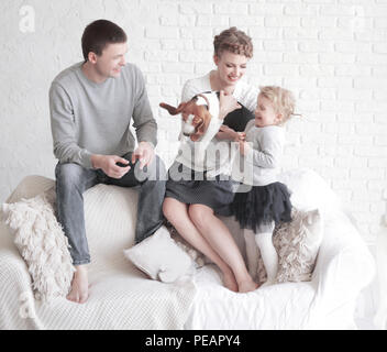 portrait of happy parents with their daughter and beloved pet with a living room - Stock Photo