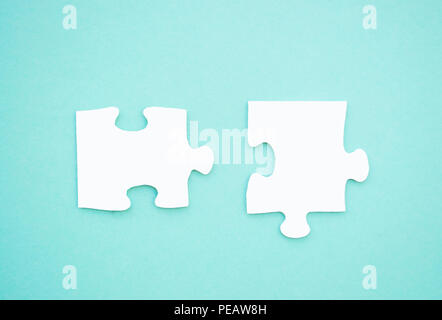 Two puzzle pieces on blue background as a symbol of autism awareness. - Stock Photo