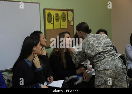 U.S. Army Staff Sgt. Sara Motyka, a Connecticut National Guard Soldier deployed to Kosovo with 1st Battalion, 169th Aviation Regiment, demonstrates the technique for finding a pulse during a Nov. 14, 2015, CPR certification class for teachers and caregivers at the PEMA Daycare Center in Pristina, Kosovo. PEMA provides professional social services for children with disabilities as well as educational classes to the parents, families and caregivers. (U.S. Army photo by Sgt. Gina Russell, Multinational Battle Group-East) - Stock Photo