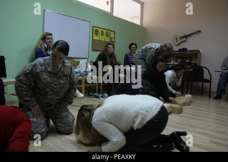 U.S. Army Staff Sgt. Sara Motyka (left) and Capt. Kimberly Keyser, both military medical professionals deployed to Kosovo with Multinational Battle Group-East, observe teachers and caregivers practicing CPR chest compressions during a Nov. 14, 2015, CPR certification class at the PEMA Daycare Center, in Pristina, Kosovo. PEMA provides professional social services for children with disabilities as well as educational classes to the parents, families and caregivers. (U.S. Army photo by Sgt. Gina Russell, Multinational Battle Group-East) - Stock Photo