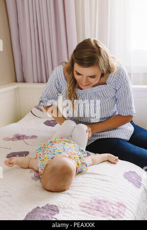 Group portrait of beautiful young white Caucasian mother and baby together on bed in bedroom doing physical fitness exercises yoga together early deve - Stock Photo