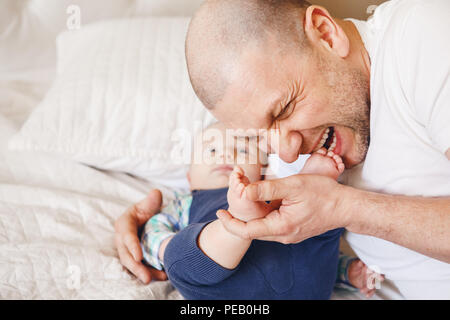 Funny portrait of middle age Caucasian father in white t-shirt lying in bed with newborn baby son kissing biting his feet toes, parenting childhood bo