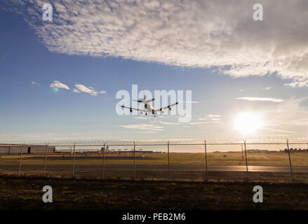 An aircraft on final at YVR with the sunset in the background. - Stock Photo