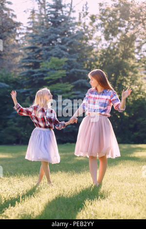 Portrait of two smiling funny Caucasian girls sisters in plaid shirt and pink tutu tulle skirt, standing dancing barefoot on grass in park forest mead - Stock Photo