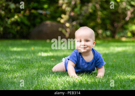 Cute little blond baby boy crawling on fresh green grass. Kid having fun making first steps on mowed natural lawn. Happy and healthy childhood concept - Stock Photo