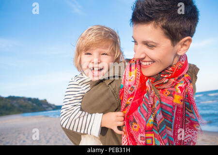Group portrait of smiling white Caucasian mother and daughter baby girl, piggy back riding, playing running on ocean sea beach at sunset outdoors, hap - Stock Photo
