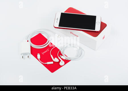 BURGAS, BULGARIA - AUGUST 11, 2018: Apple iPhone 7 Plus Red Special Edition on white background, front view. Charger, earpods and adapter. - Stock Photo