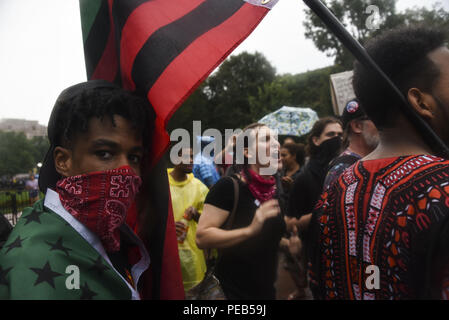 Washington D.C, USA. 12th Aug, 2018. Members of Antifa chant as police protect white nationalists at the Unite the Right 2 rally in Washington, DC.Despite predictions of a huge rally by the Alt-Right celebrating the first anniversary of the Unite The Right rally in Charlottesville, Virginia, only 15 showed up to march in Washington, DC on Saturday August 12. The small group was met by over a thousand anti-fascist protesters who marched from the city's Freedom Plaza to meet the handful of white supremacists who gathered under police guard under at a park behind the White House. - Stock Photo