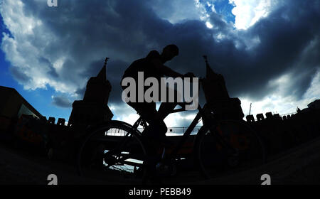 Germany, Berlin. 14th Aug, 2018. A cyclist and the Oberbaum Bridge can be seen as a silhouette in front of a dark band of clouds. Credit: Paul Zinken/dpa/Alamy Live News - Stock Photo