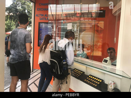 (180814) -- ISTANBUL, Aug. 14, 2018 (Xinhua) -- People exchange money at a currency exchange office in Istanbul, Turkey, on Aug. 14, 2018. Turkish President Recep Tayyip Erdogan announced Tuesday to boycott U.S. electronic products amid an ongoing and deepening rift between the two NATO allies over a number of issues. Erdogan reiterated that the recent plunge of Turkish lira and stocks was caused by an economic attack by U.S. President Donald Trump and his administration. The Turkish lira has recovered against the dollar and euro early Tuesday, up more than 4.5 percent at 6.57 lira against one - Stock Photo