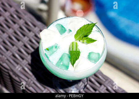 Blue cocktail in a pot-bellied glass with ice cream and green mint leaves - Stock Photo