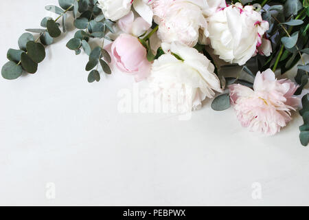 Styled stock photo. Decorative still life floral composition. Wedding or birthday bouquet of pink and white peony flowers and eucalyptus branches. White table background. Flat lay, top view. - Stock Photo