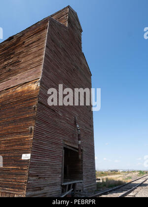An old, rundown, damaged wooden grain elevator in rural Montana situated by train tracks. - Stock Photo
