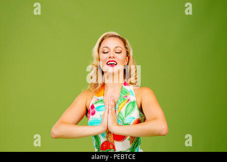 Beautiful woman with hands together in prayer and mouth open, isolated on green studio background - Stock Photo