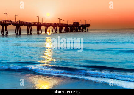 Oceanscape of the Pompano Pier and the Atlantic Ocean early morning during surise. Light surf, blue water and an orange sky on the ocean. - Stock Photo