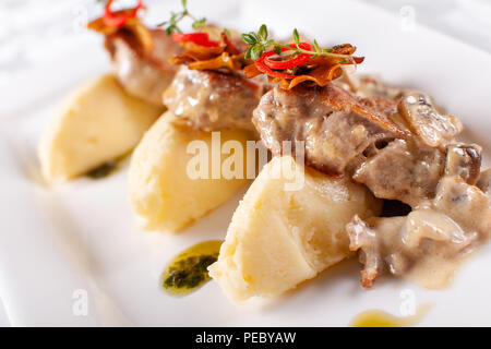 Pork Medallions with Mashed Potato and Mushrooms. Pork tenderloin on a white plate, good serving. restaurant menu - Stock Photo