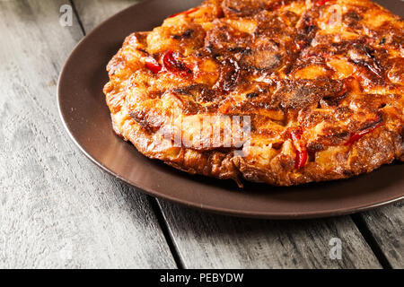 Tortilla de patatas. Spanish omelette with sausage chorizo, potatoes, paprika and egg, accompanied by olive oil. Spanish cuisine - Stock Photo