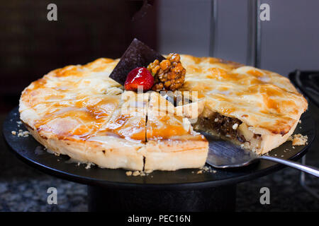 Walnut pie with raspberries, decorated with fresh strawberries, on black background - Stock Photo