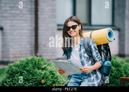 happy young woman with backpack holding map and smiling at camera - Stock Photo