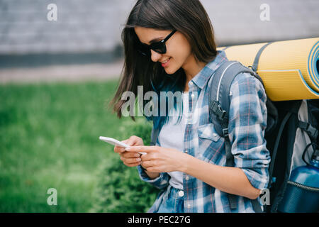 smiling young woman with backpack using smartphone - Stock Photo