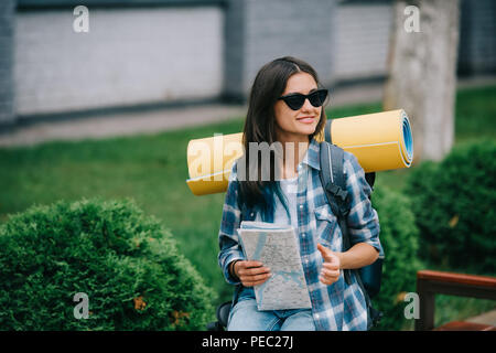 happy young woman traveler in sunglasses holding map - Stock Photo