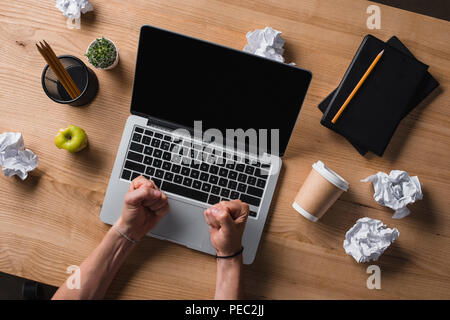 cropped shot of angry stressed businessman sitting at workplace with laptop - Stock Photo
