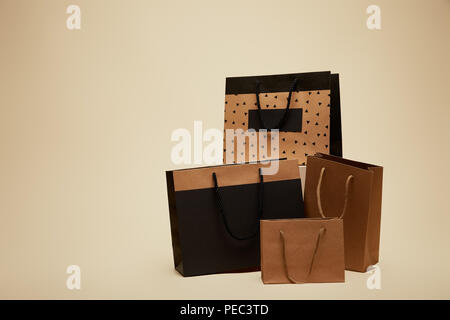 four different shopping bags isolated on beige - Stock Photo