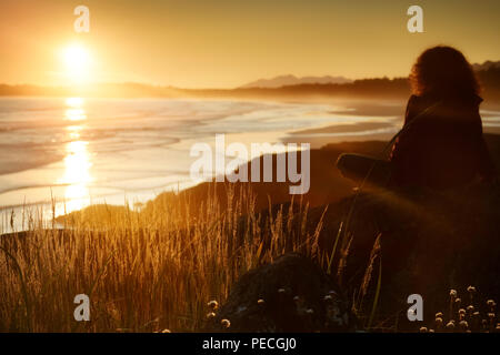 Woman watching a beautiful sunset on a shore of Pacific Rim National Park while the glowing sun is setting behind the Pacific ocean. Tofino, Vancouver - Stock Photo