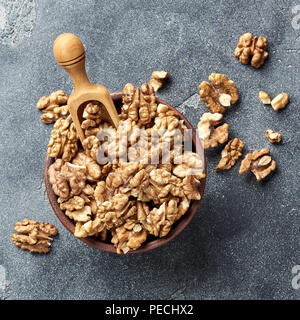 Walnut kernels with wooden scoop on gray background. Nuts in clay bowl. Top view. - Stock Photo