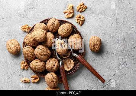 Whole walnuts and kernels on gray background and nutcracker. - Stock Photo