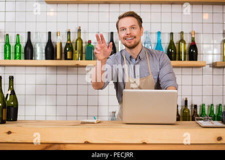 Cafeteria worker. Positive handsome bearded man wearing apron and standing at the counter while working in the cafeteria - Stock Photo
