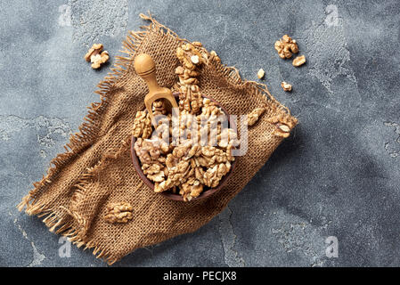 Walnut kernels wooden scoop on gray background with copy space. Nuts in clay bowl. Top view. - Stock Photo