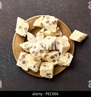 Eastern delicacy. Halva, sweetness, dessert on brown background. - Stock Photo