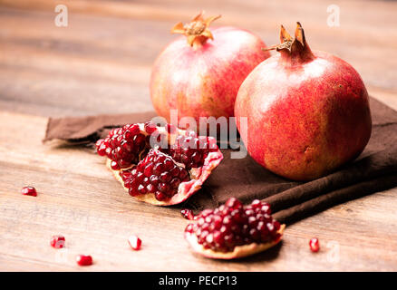Pomegranate fruits with grains on wooden table. - Stock Photo